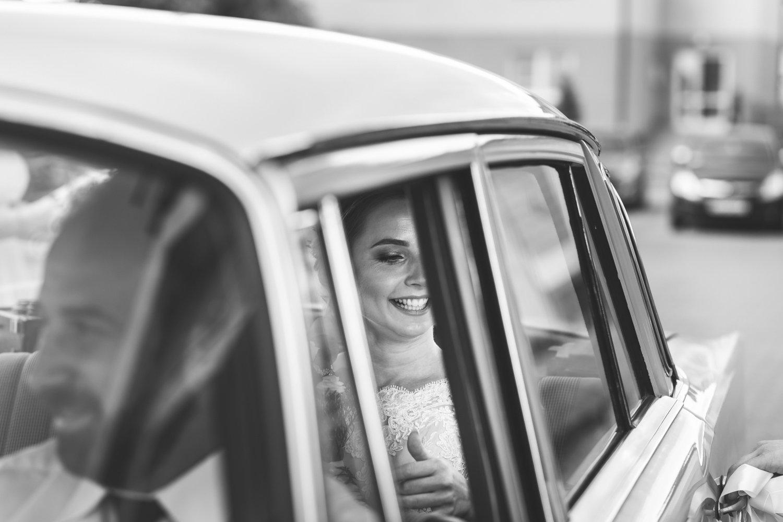 Panna młoda w drodze na ślub. Ujęcie przez okno zabytkowego mercedesa